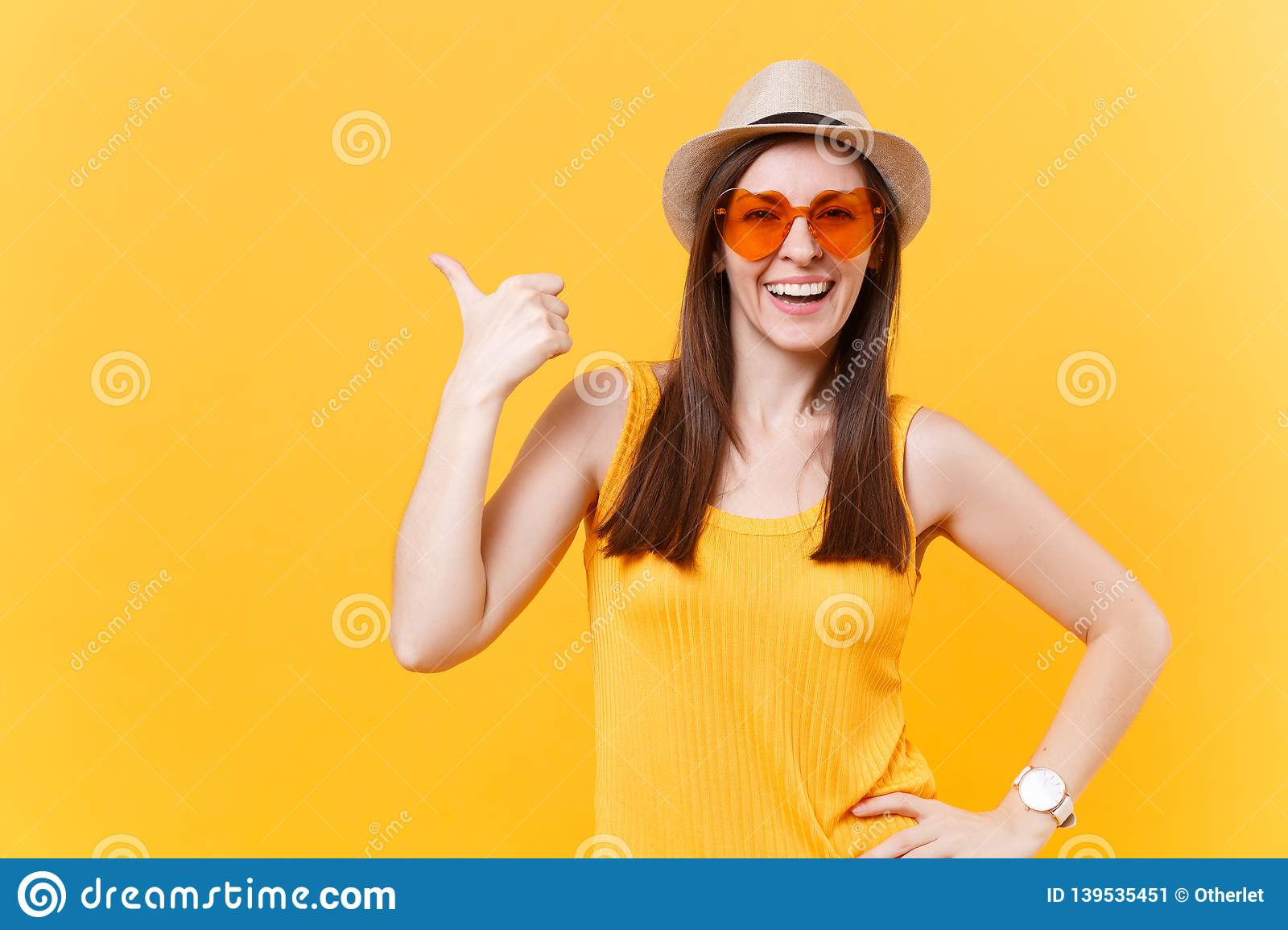 Portrait of smiling young woman in straw summer hat, orange glasses pointing right hand aside copy space isolated on