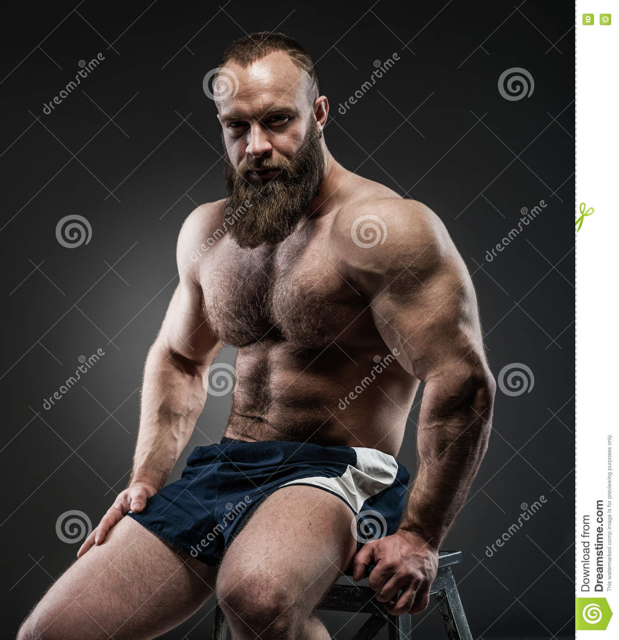 Portrait of strong bearded man with perfect abs, pecs shoulders,biceps, triceps and chest