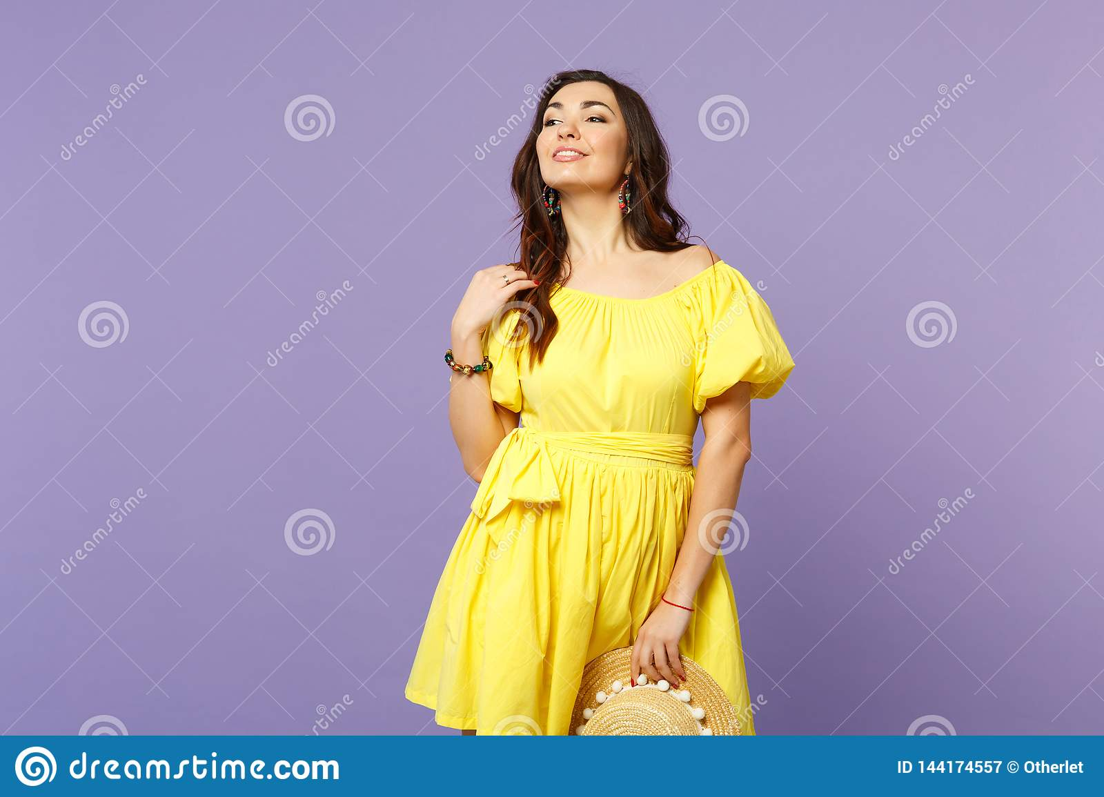 Portrait of stunning young woman in yellow dress holding summer hat looking aside on pastel violet wall