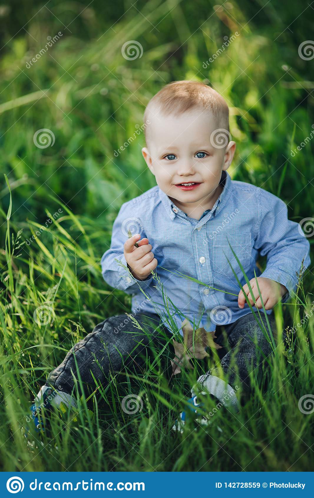 Portrait of stylish blonde little boy sitting in park among grass. Portrait of stylish blonde little boy, wearing in checkered shirt and jeans sitting in park at royalty free stock images