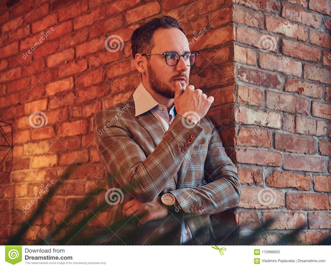 Portrait of a stylish man in a flannel suit and glasses leaning against a brick wall in a room with loft interior.