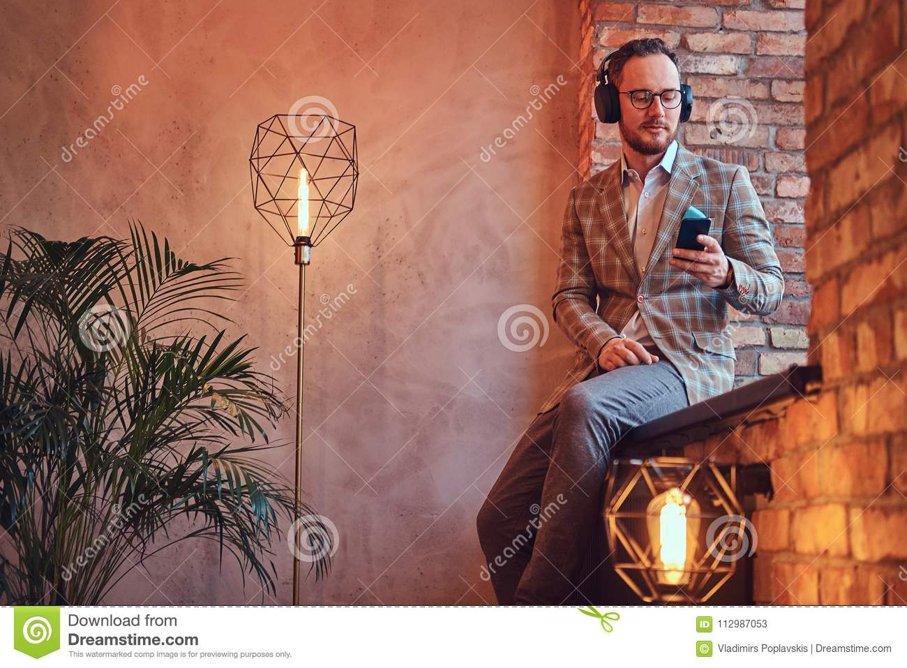 Portrait of a stylish man in a flannel suit and glasses listening music with the phone and headphones sitting on a