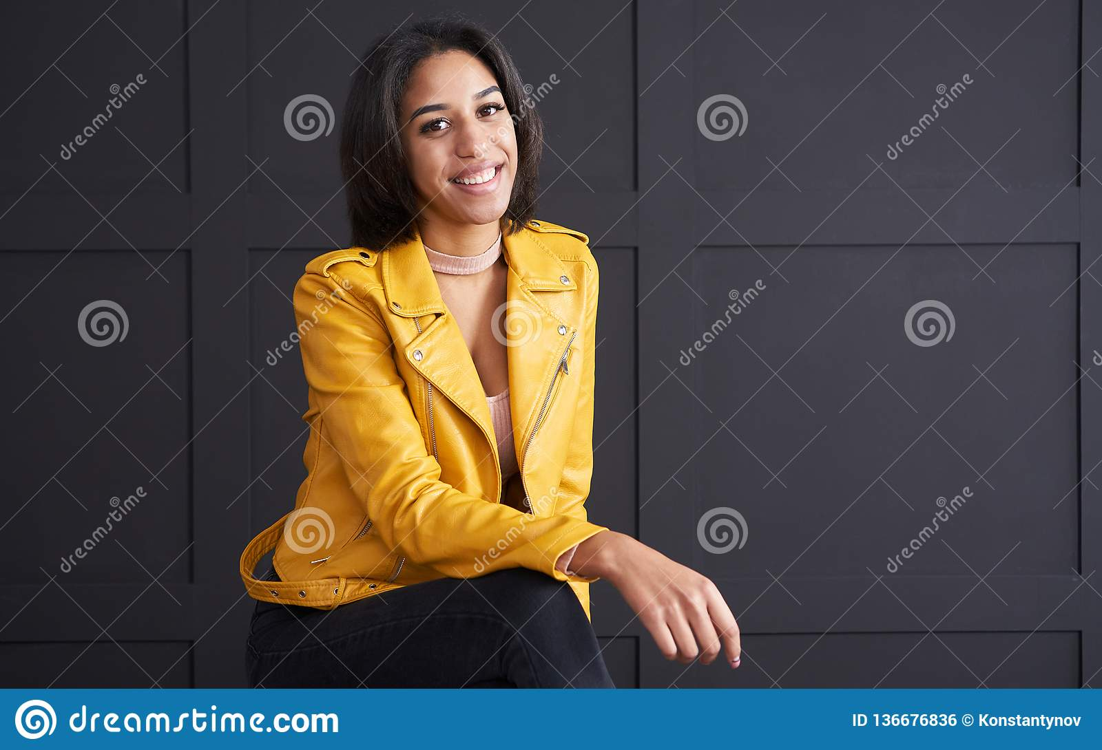 Teenage girl smiling in yellow leather jacket