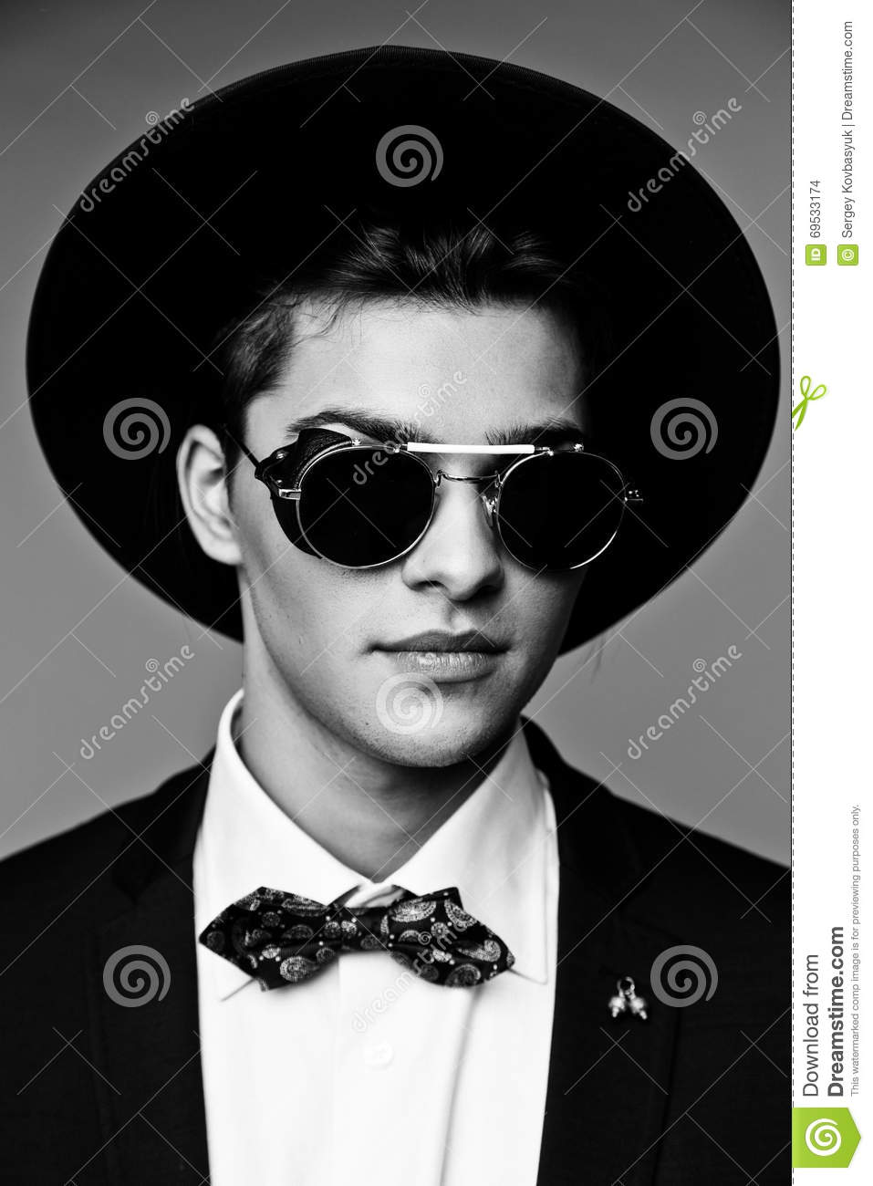 f49d0eb1d62 Portrait of a stylish young man in hat wearing elegant suit and sunglasses.  Download preview