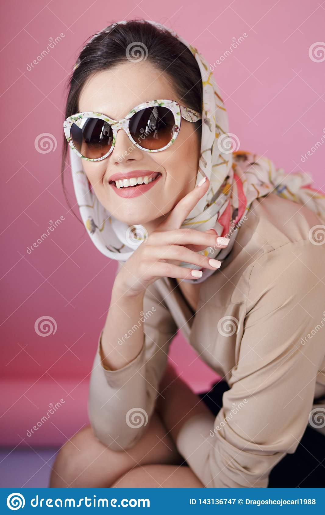 Cheerful beautiful woman earrings in fashionable eyeglasses and delicate silk scarf,  on a pink background.