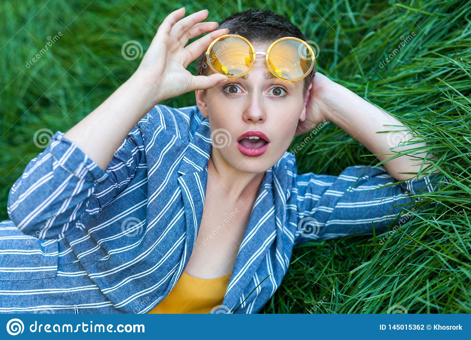 Portrait of surprised cute young woman with short hair in casual blue striped suit lying down on green grass, hoding yellow