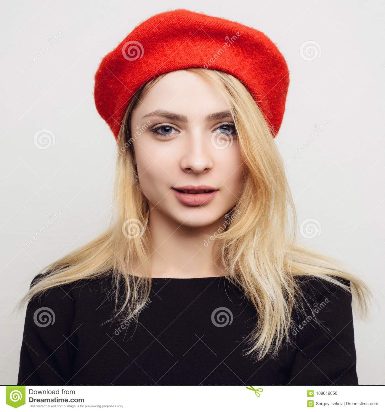 0494a345005 Portrait of a surprised young blond woman in a red beret on a white  background.
