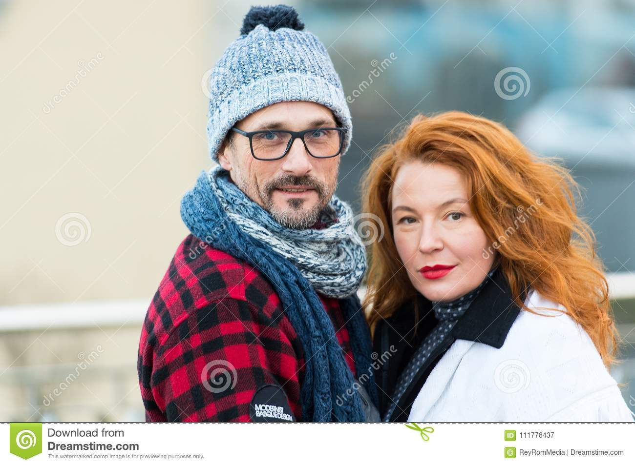 Portrait of sweet couple on street. Smiled man and happy woman posing for picture. Portrait of urban family. Red hair woman and ga