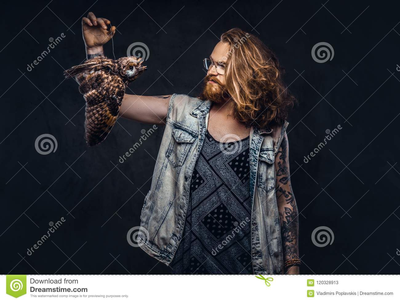 Portrait of a tattoed redhead hipster male with long luxuriant hair and full beard dressed in a t-shirt and jacket holds