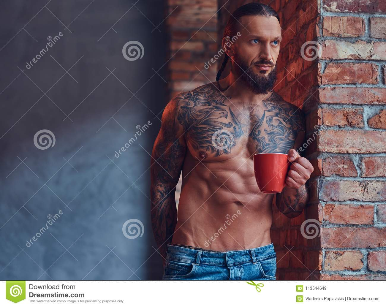 Portrait of a tattoed shirtless male with a stylish haircut and beard, drinks morning coffee, leaning against a brick