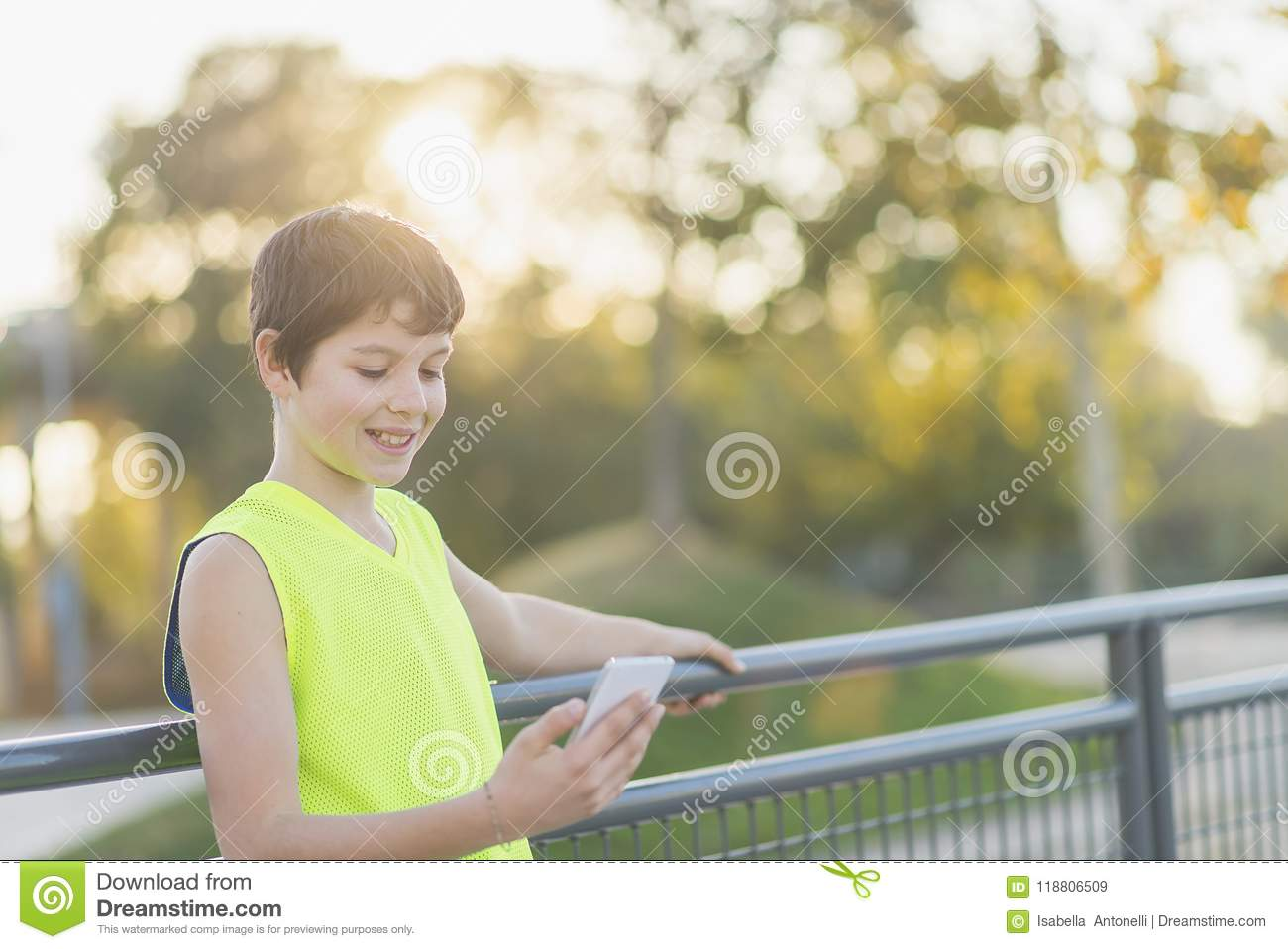 Portrait of a teenager smiling looking his smartphone