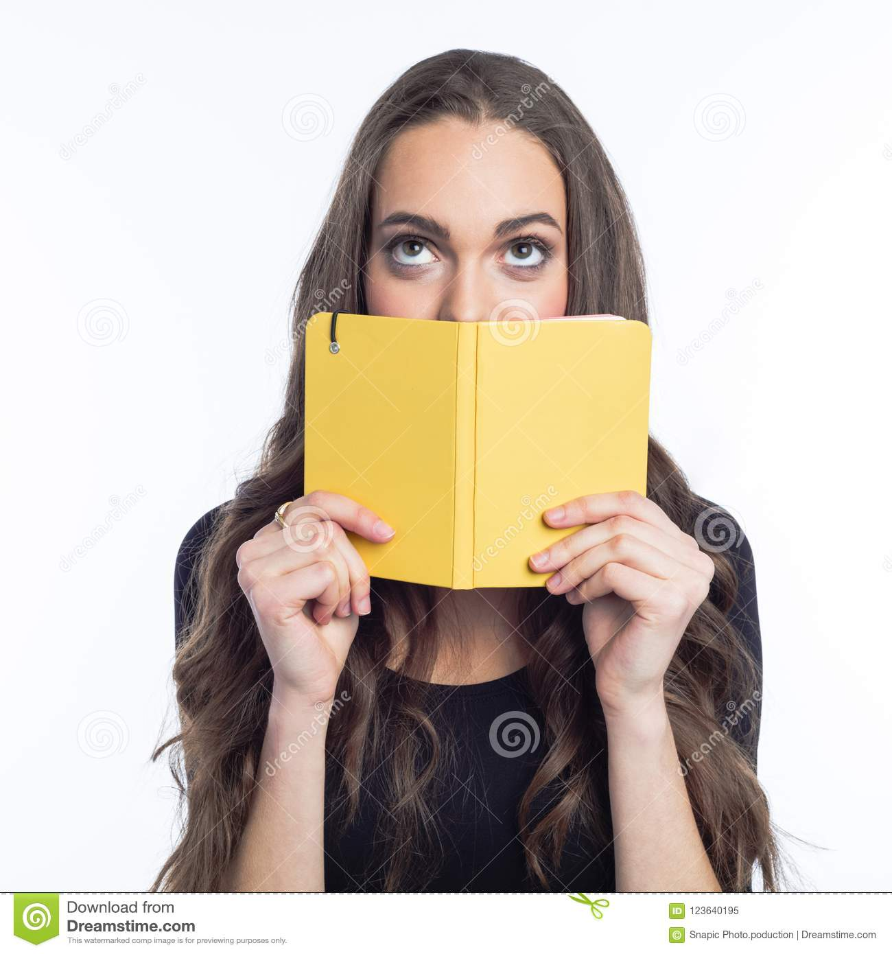 Portrait of thinking young woman holding yellow notebook