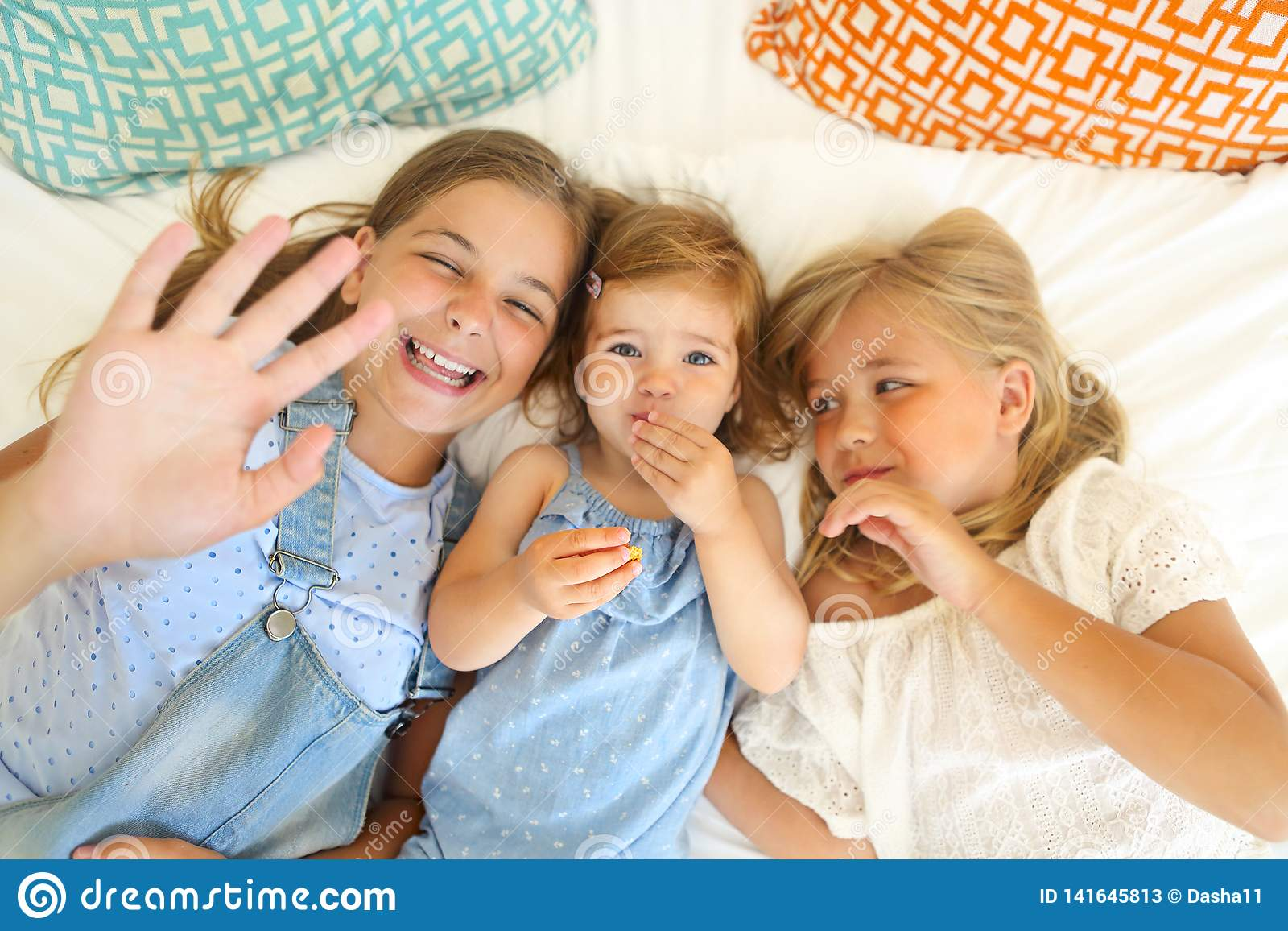 Three happy little sisters on a bed having fun