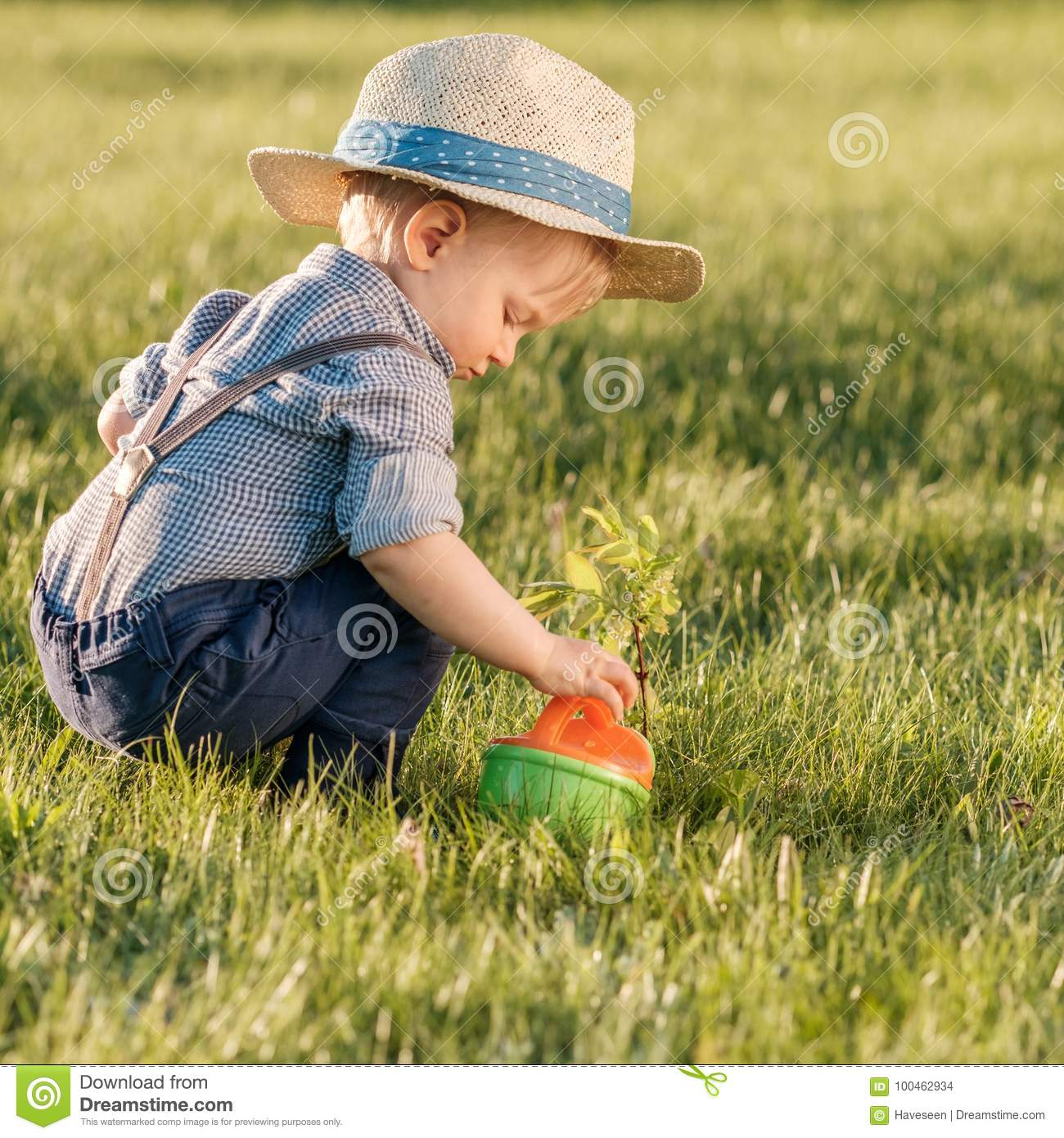 Rural scene with one year old baby boy wearing straw hat using watering can 252088ef9af