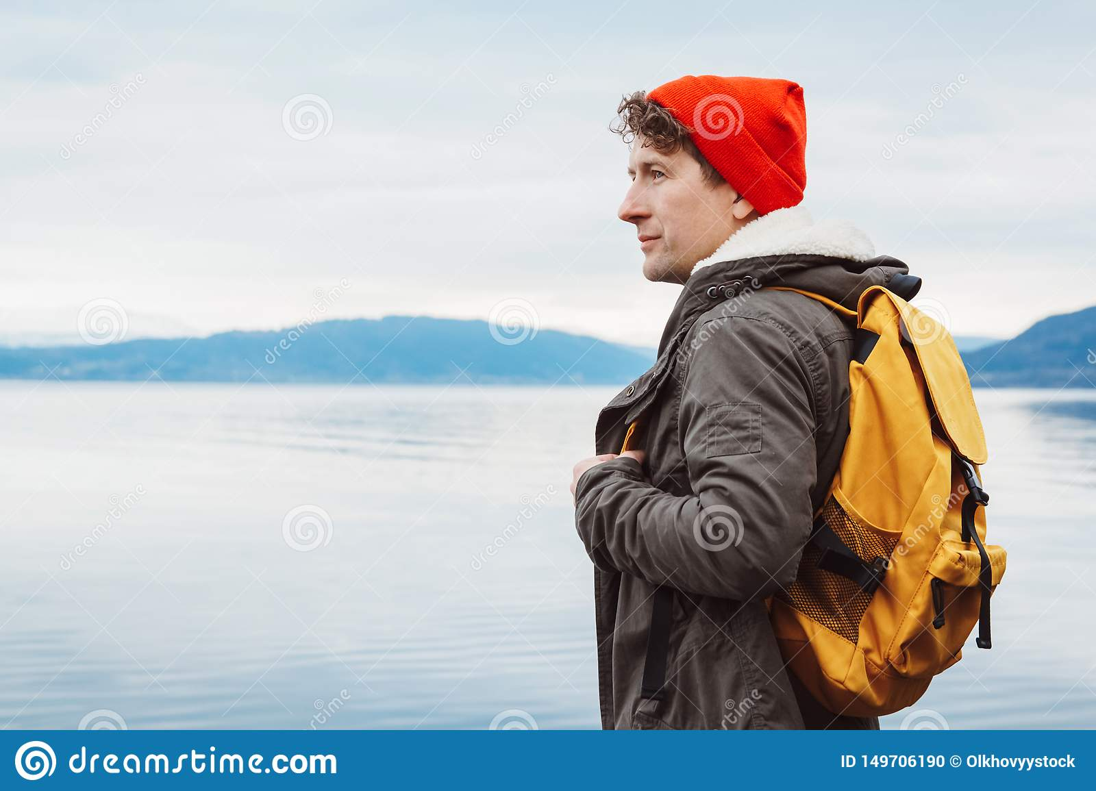 Portrait traveler man with a yellow backpack wearing a red hat on the shore on the background of mountain and lake