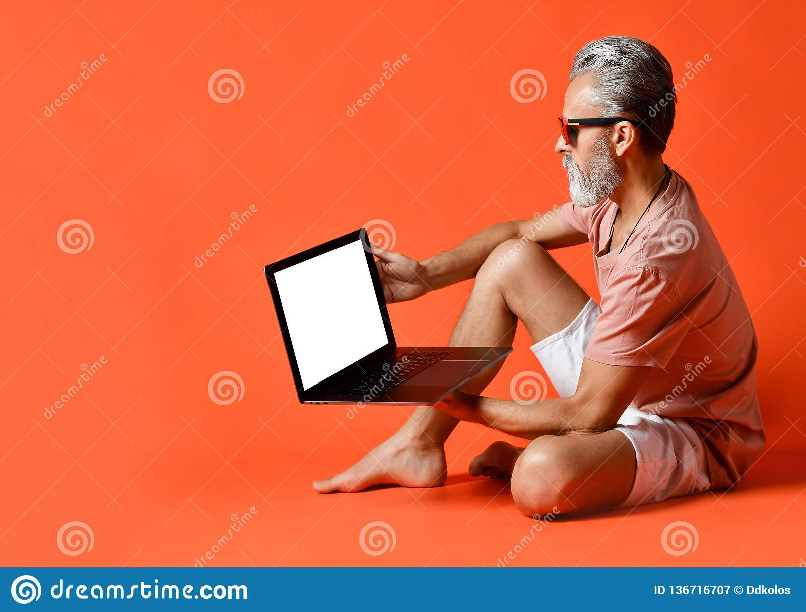 Portrait of trendy pensioner enjoying the use of new laptop