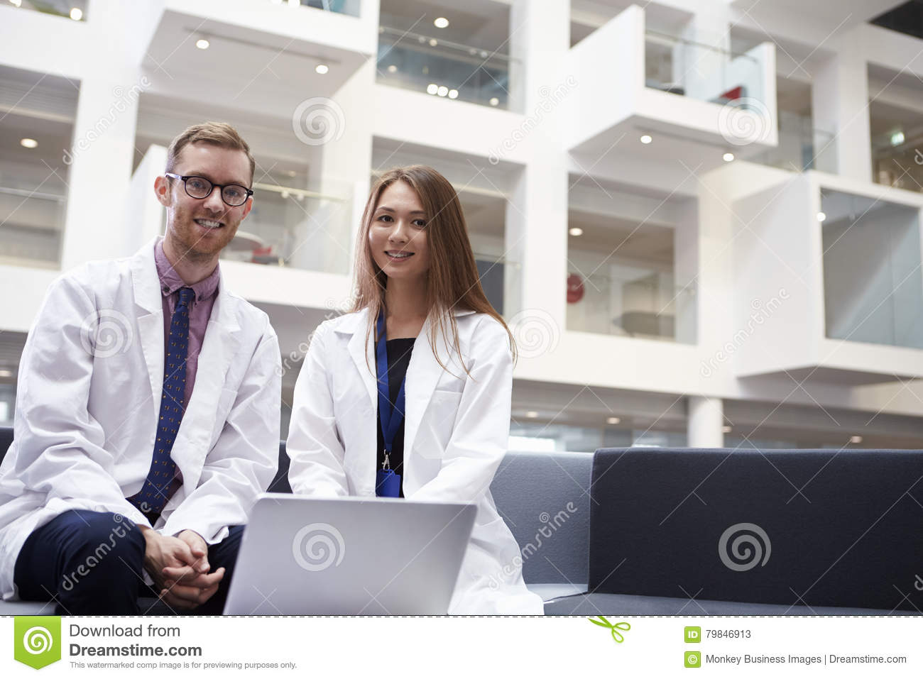 Portrait Of Two Doctors Meeting In Hospital Reception Area
