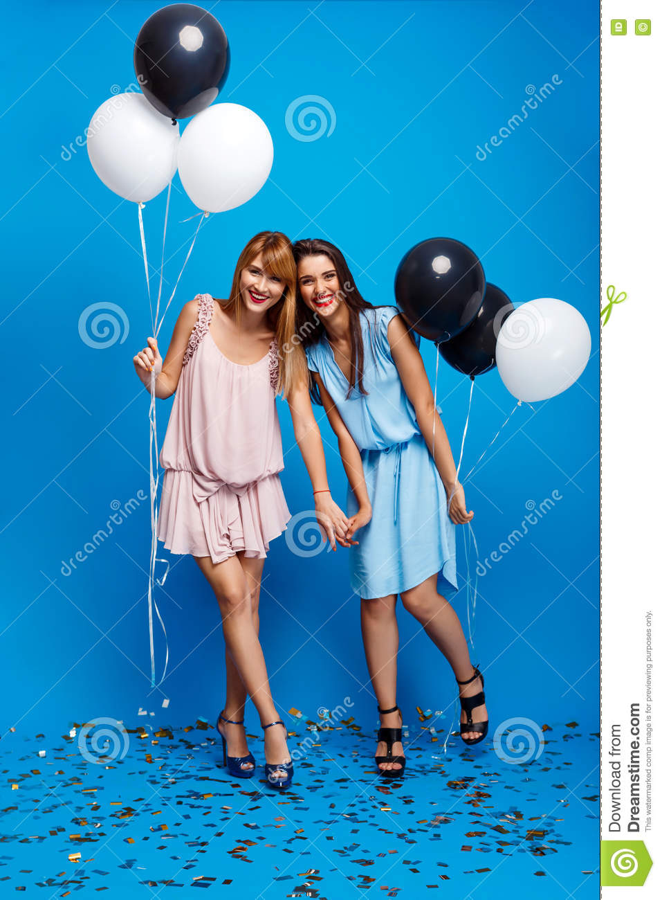 5866bdb09 Portrait Of Two Girls Resting At Party Over Blue Background. Stock ...