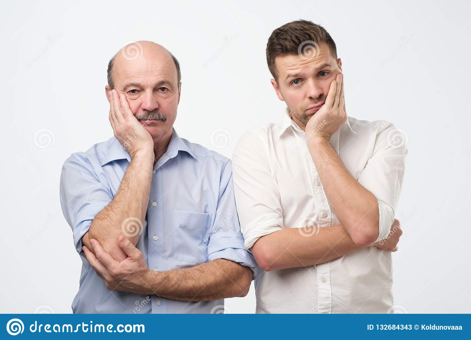 Portrait of two mature men with bored fed up expression, looks displeased up.