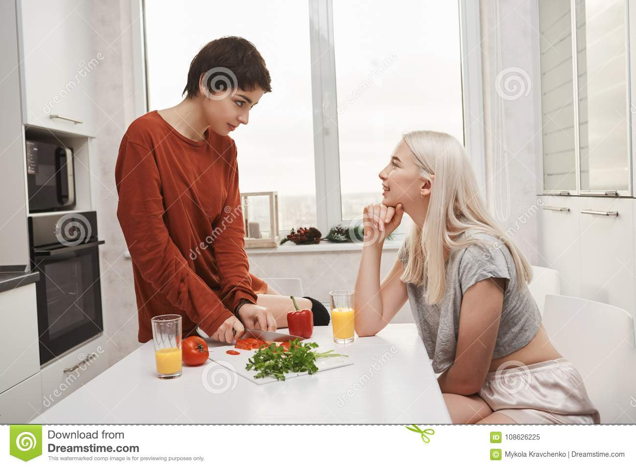 Portrait Of Two Woman Sitting In Kitchen Drinking Juice And