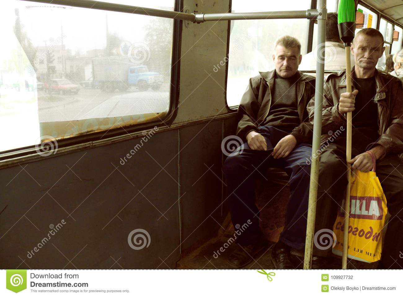 Portrait of two working class men commuting in bus
