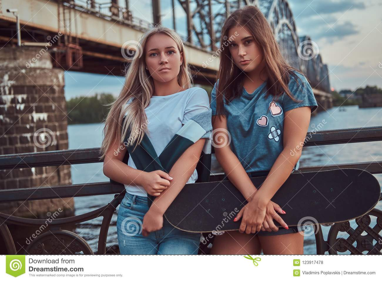 Portrait of a two young hipster girls holds a skateboard and leaning on a guardrail on a background of the old bridge.