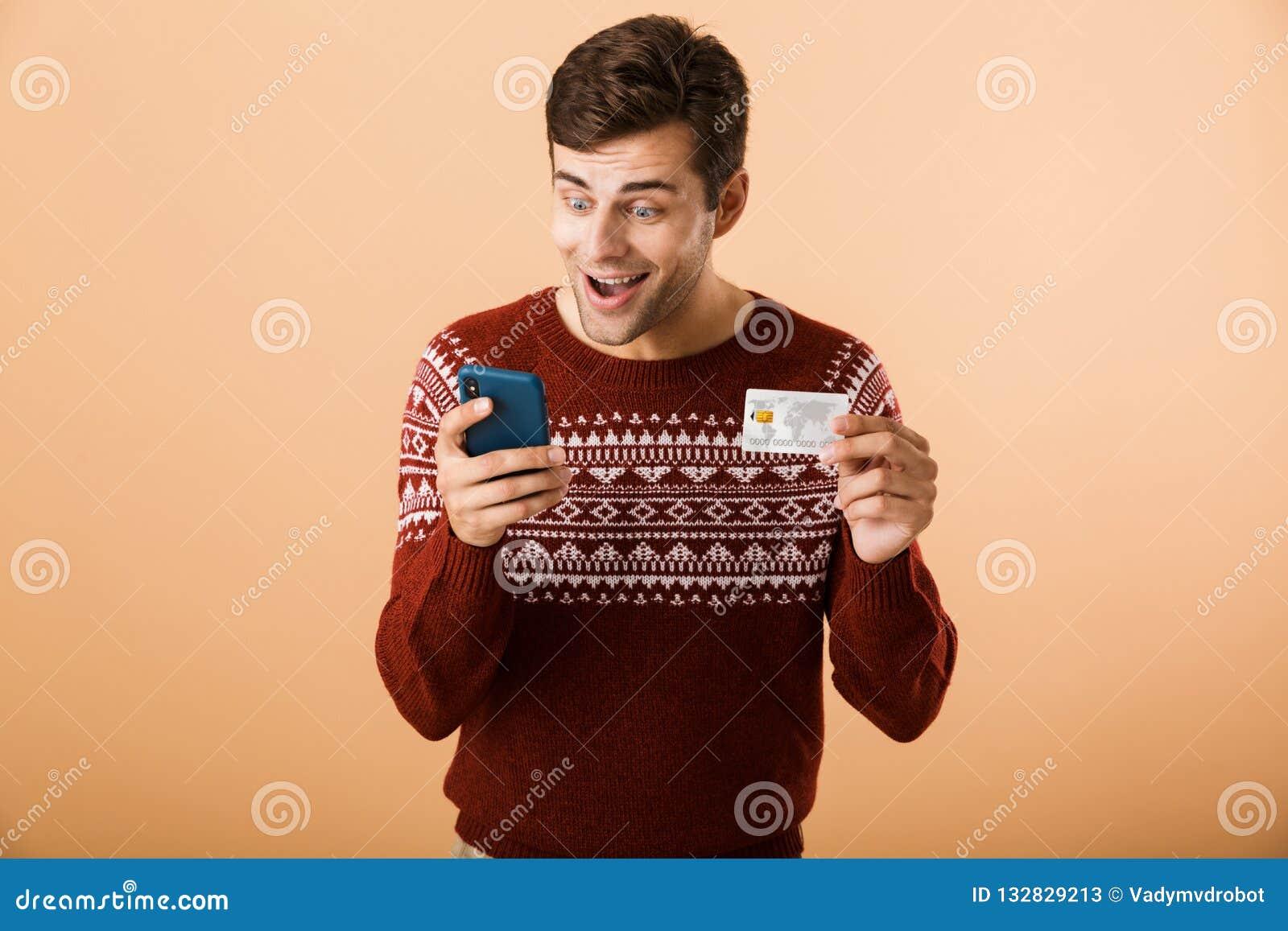 e1957689750a Portrait un jeune homme gai habillé dans la position de chandail  d isolement au-dessus du fond beige, téléphone portable de participation,  montrant la carte ...