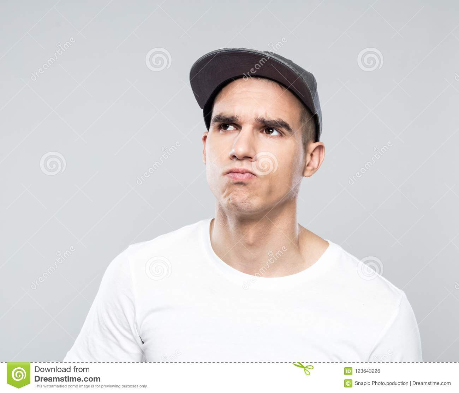 Portrait of uncertain young man in baseball cap