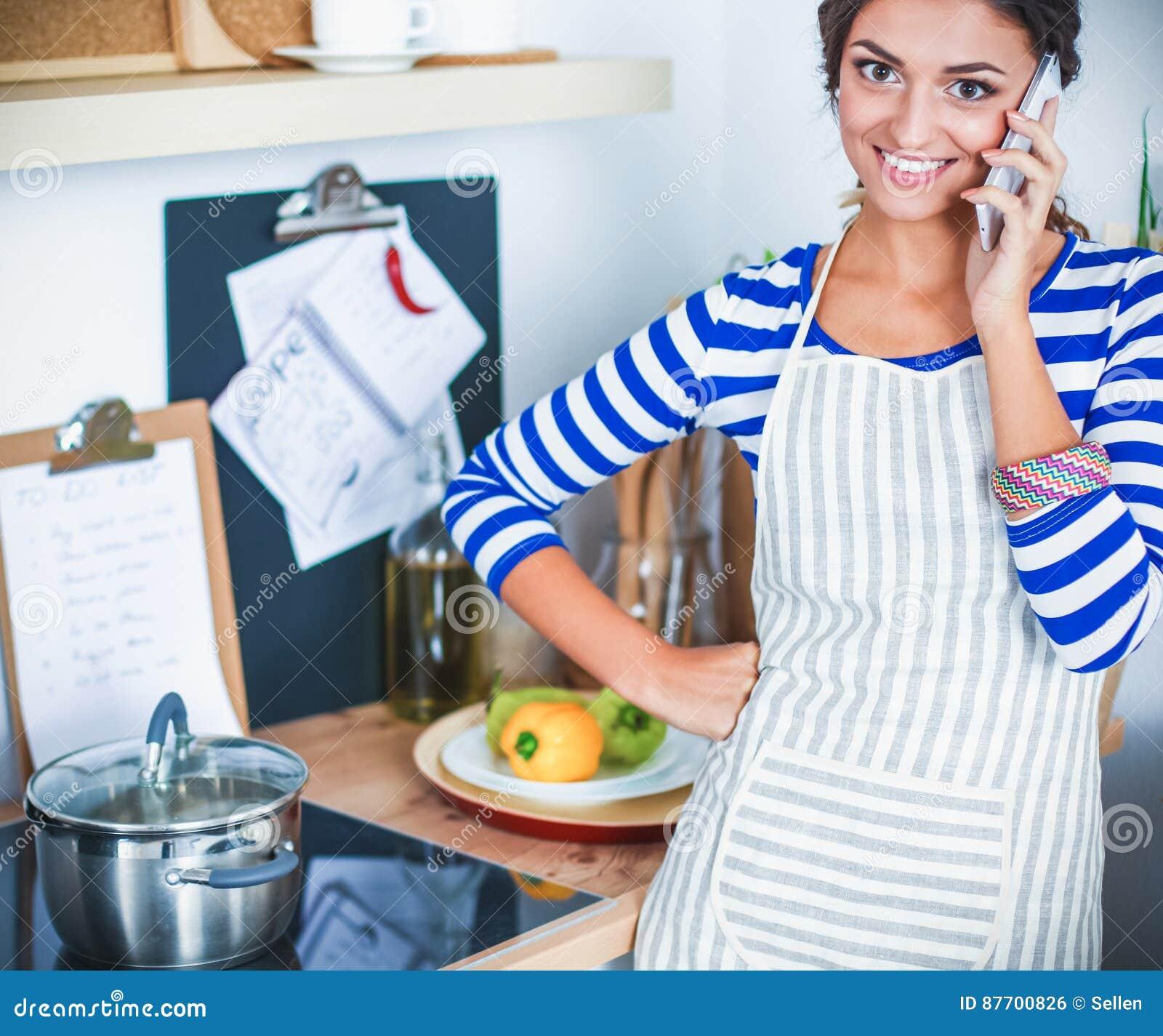 Portrait une messagerie textuelle de sourire de femme des légumes dans la cuisine à la maison