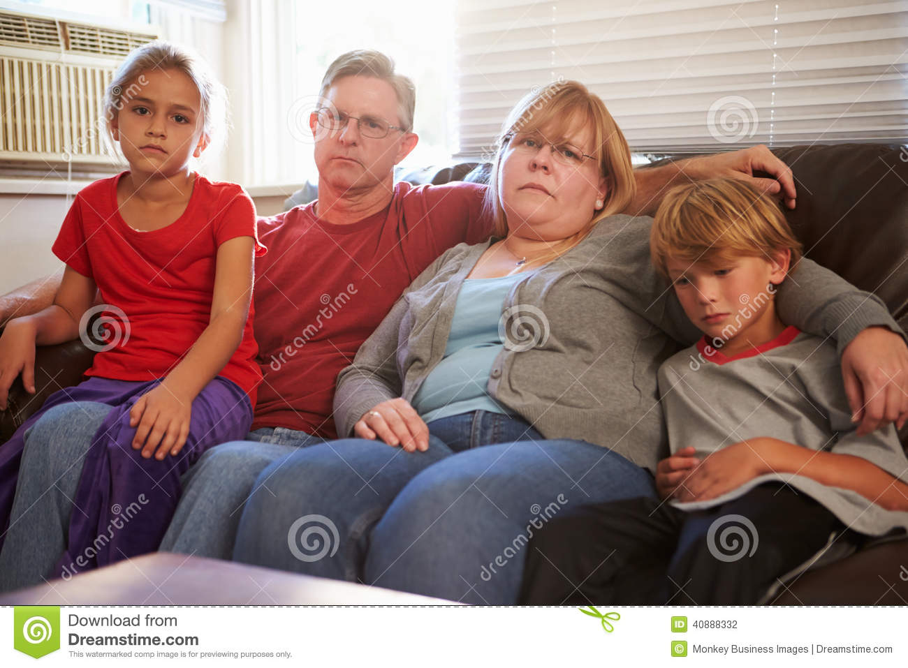 Portrait Of Unhappy Family Sitting On Sofa Together