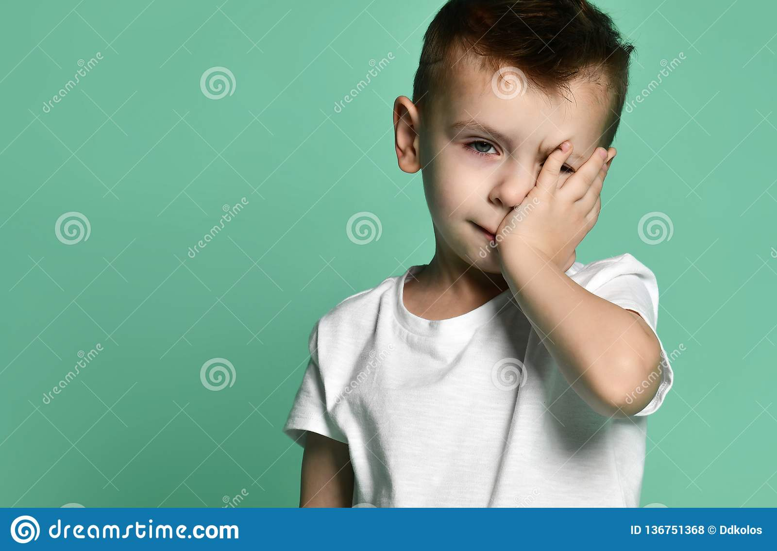Portrait of unhappy sad bored kid boy leaning head on palm looking with upset