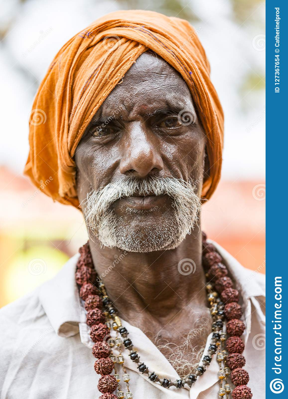 Portrait of unidentified Sadhus pilgrims man dressed in orange clothes, sitting on the road, waiting for food. It is a mass Hindu