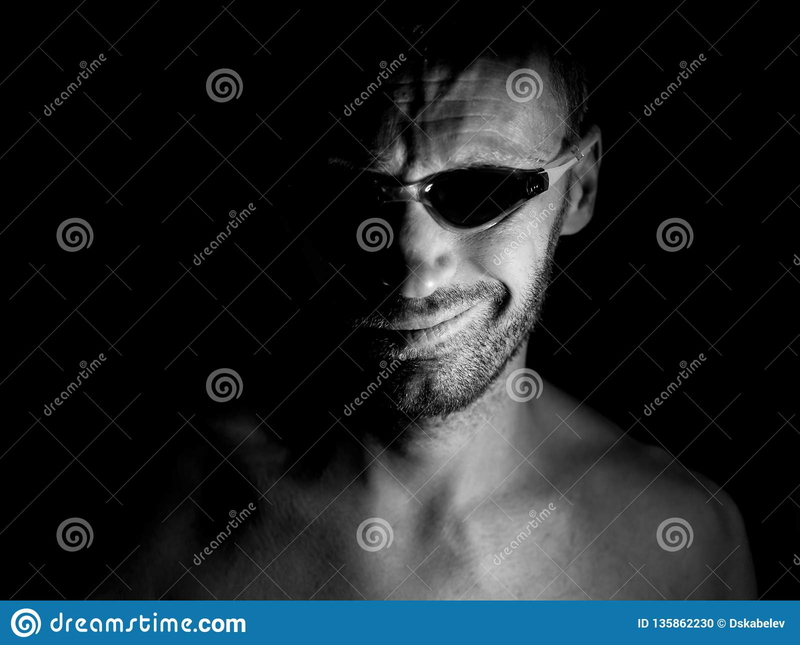 Portrait of unshaven adult caucasian man in swimming glasses. He smiles like maniac and seems like madness. Black and white shot,