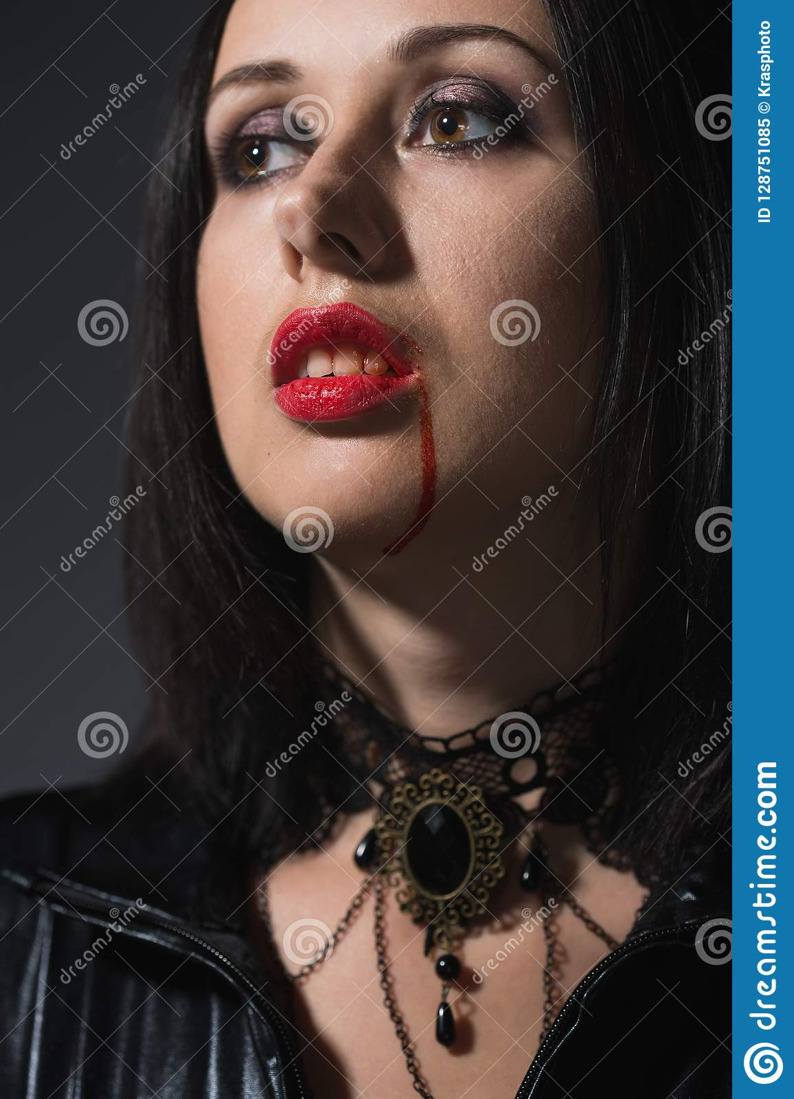 Vampire woman with a bloody mouth and teeth fangs celebrating a