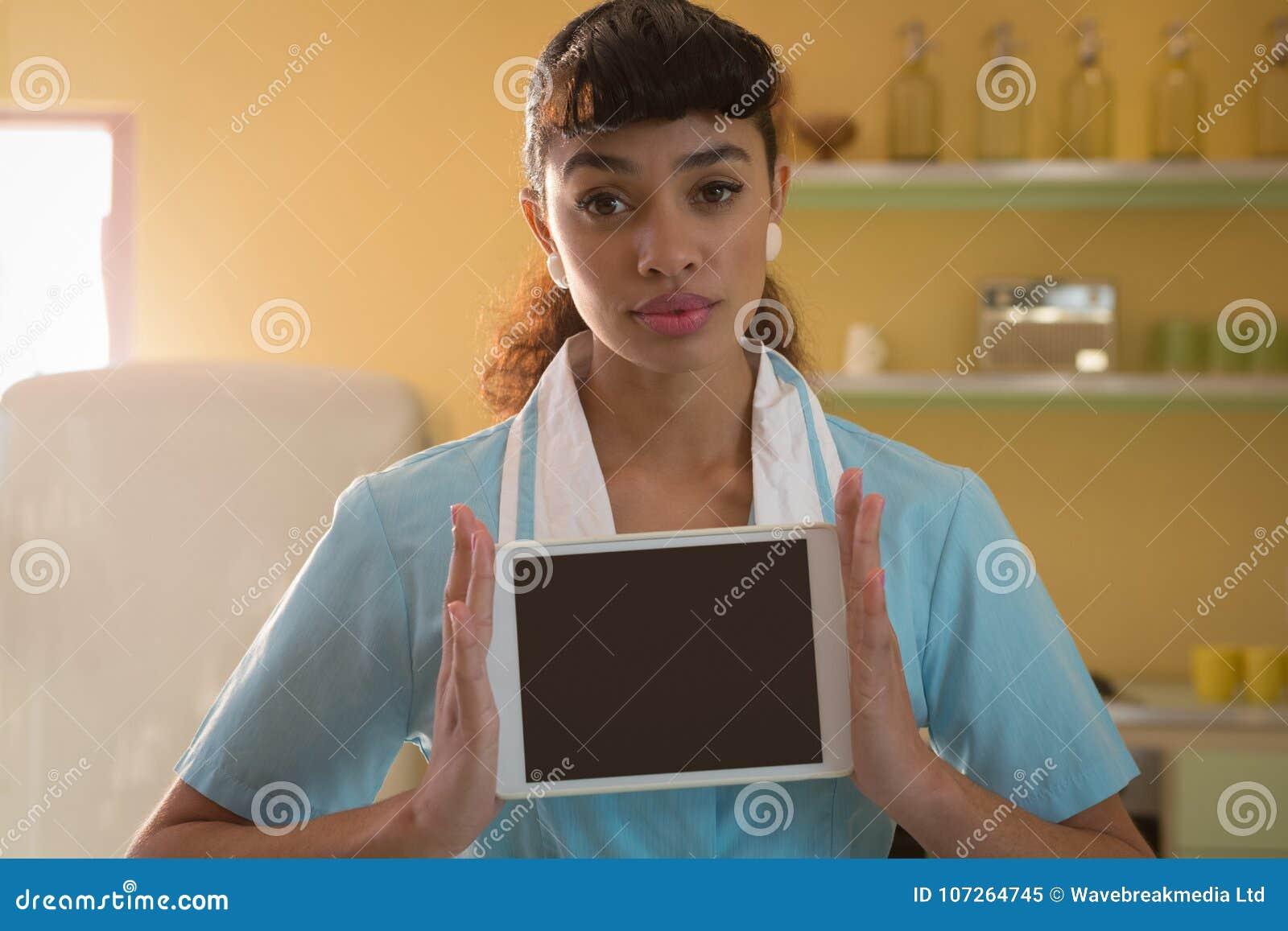 Waitress holding digital tablet in restaurant