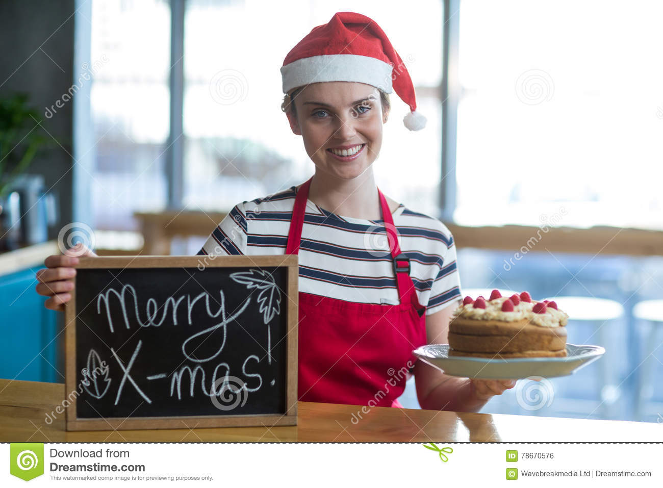 portrait of waitress holding slate with merry x-mas sign and cake