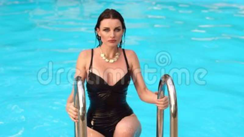 e2bbed2a993e0 Beautiful woman coming out from swimming pool.