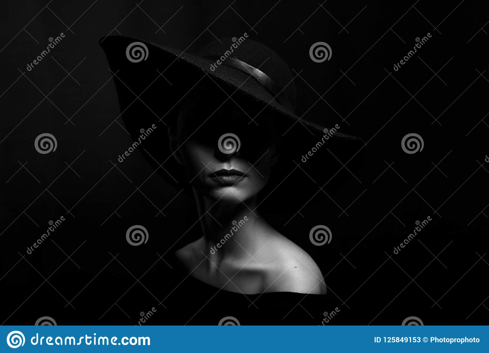 Portrait of a woman in a black hat on a black background black and white photo