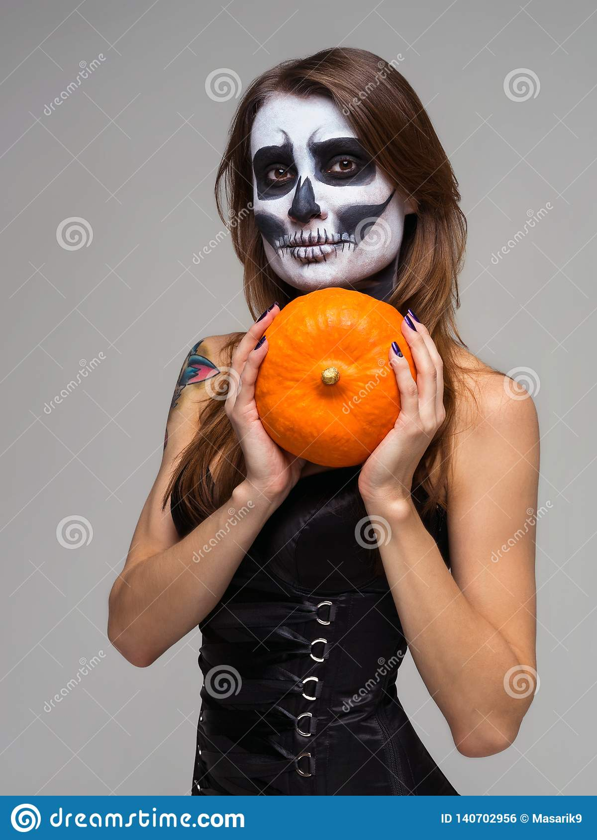 Portrait of woman with halloween skeleton makeup holding pumpkin over gray background