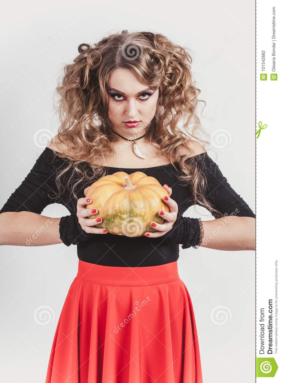 677e21b975 Portrait of woman holding in hands orange pumpkin isolated on gray  background. Wearing black blouse and red skirt. Halloween celebration.  Vertical shot