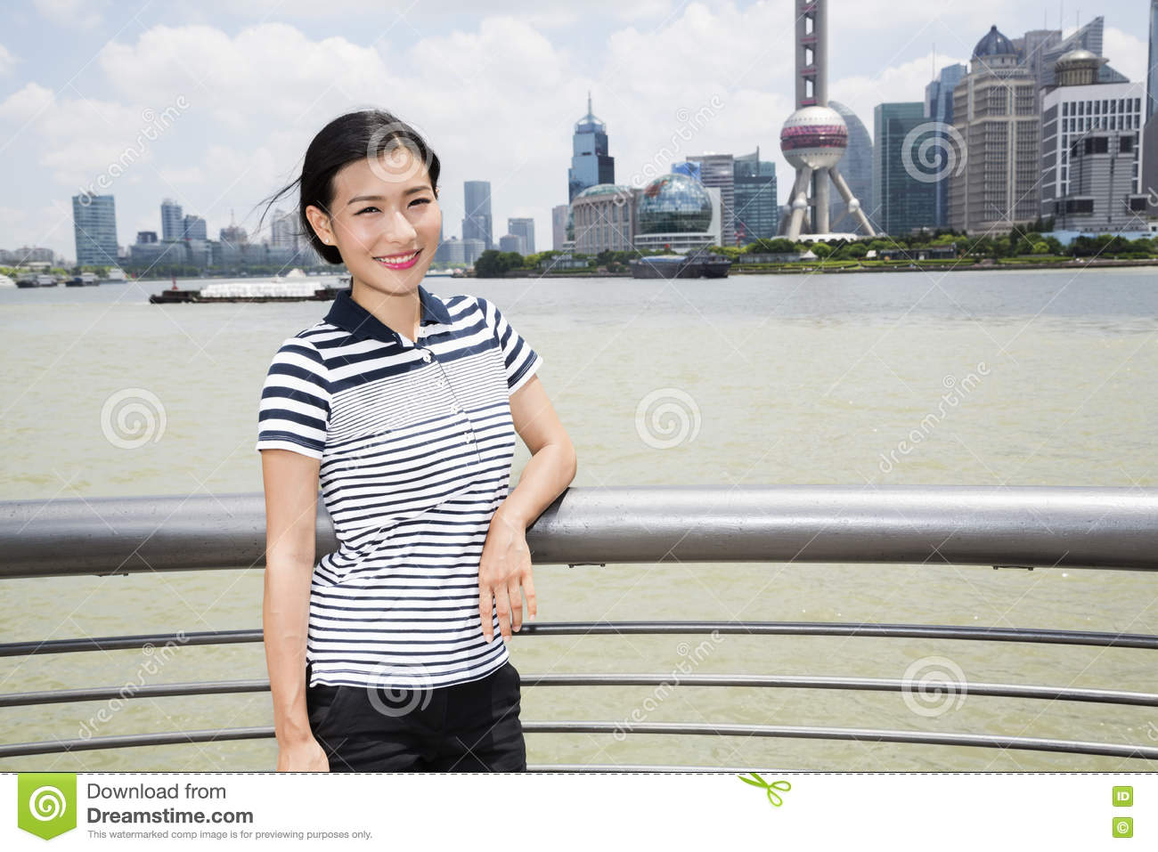 portrait of woman leaning on railing by river with oriental pearl