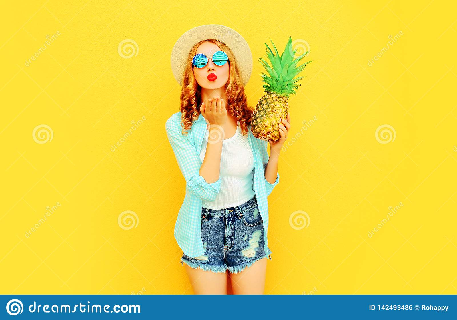 Portrait woman with pineapple sending sweet air kiss in summer straw hat, sunglasses, shorts on colorful yellow