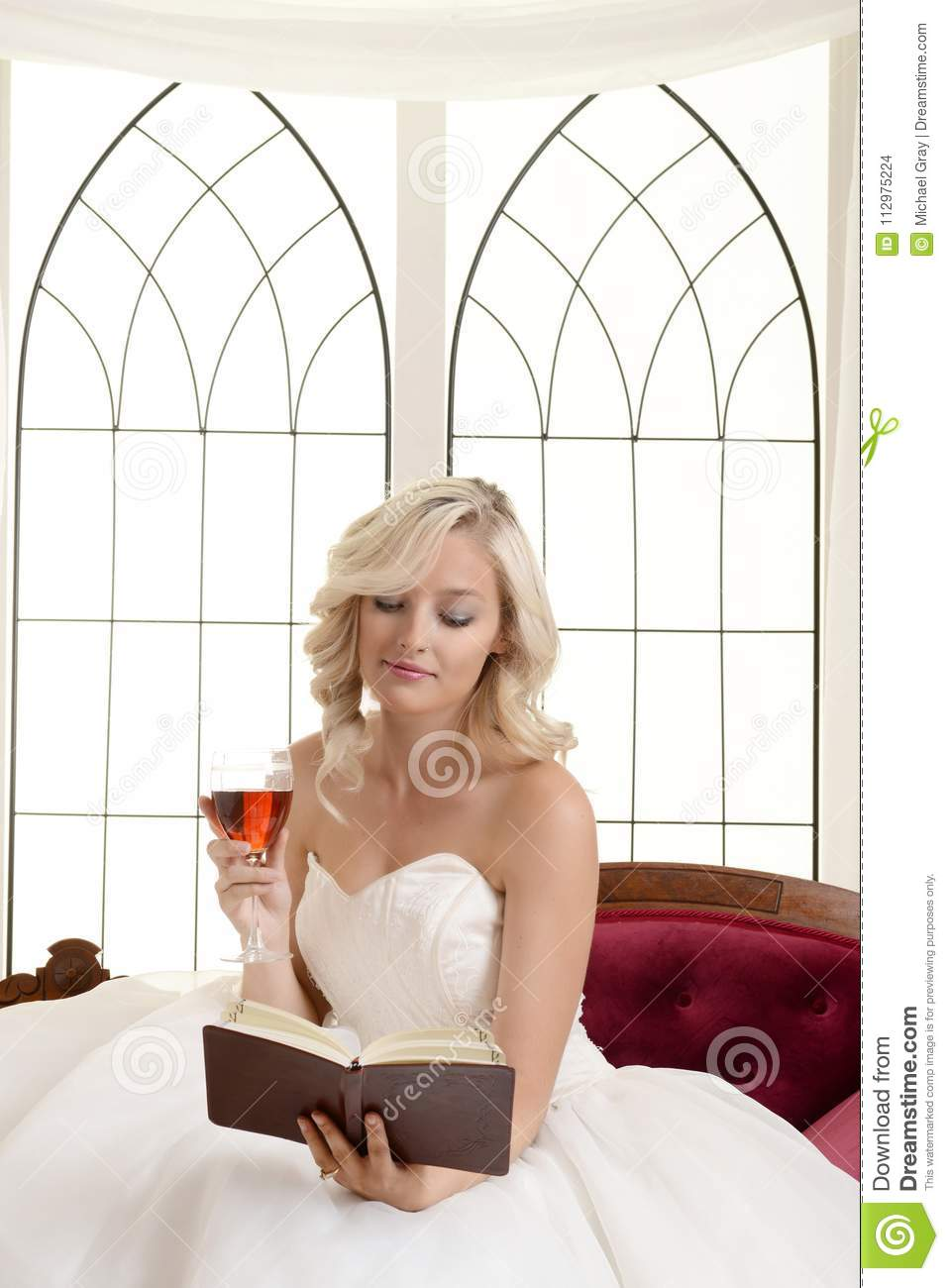 Woman reading book holding glass red wine