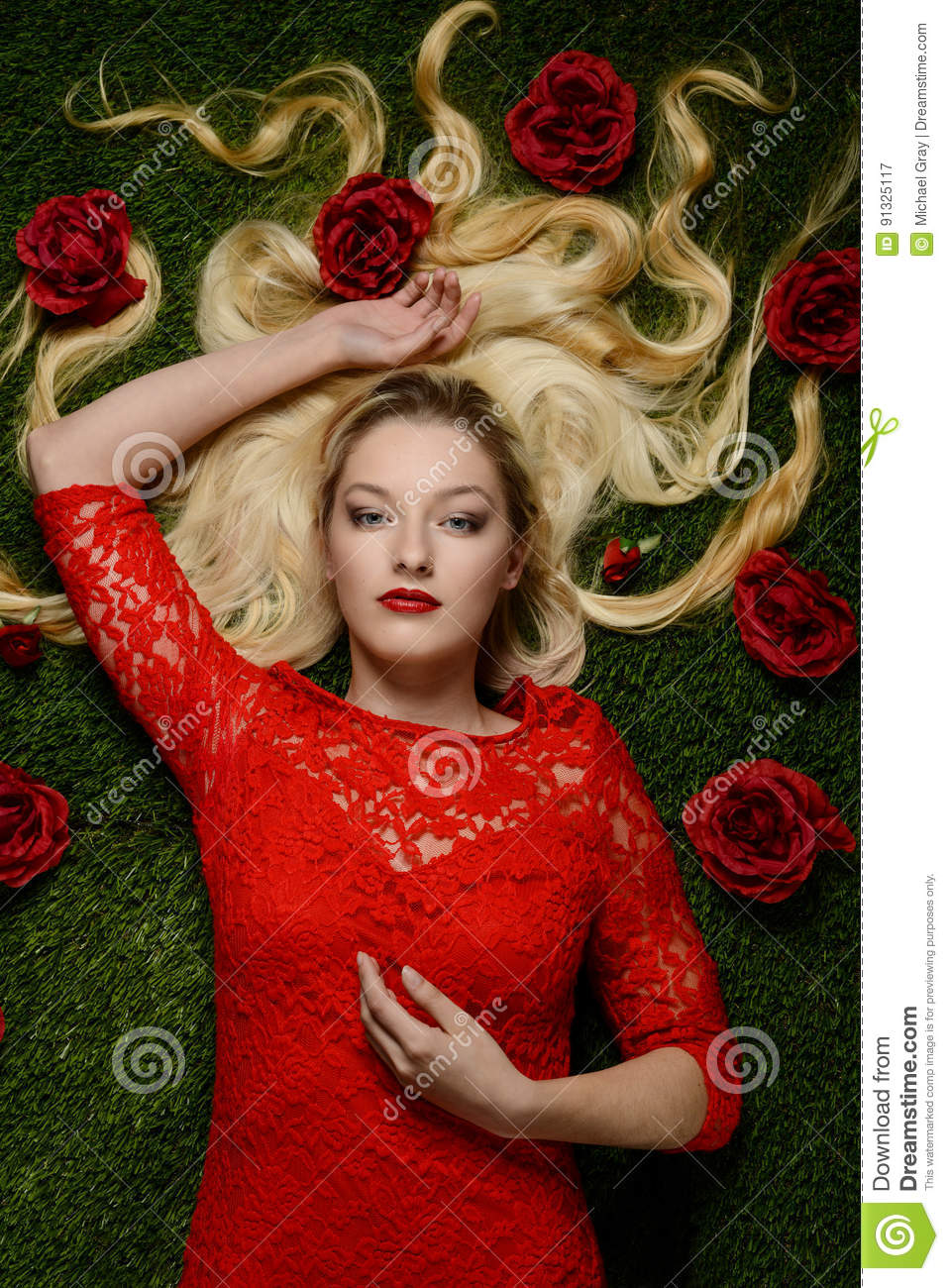 Portrait of woman in red dress laying in grass with roses