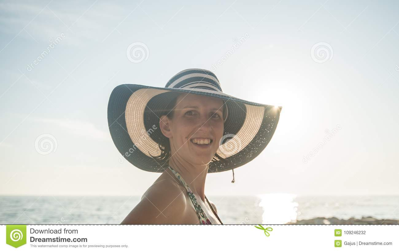 Portrait of a woman with wet hair wearing striped straw hat and swimsuit at  the beach at sunset during summer vacations. a6addf6b125b