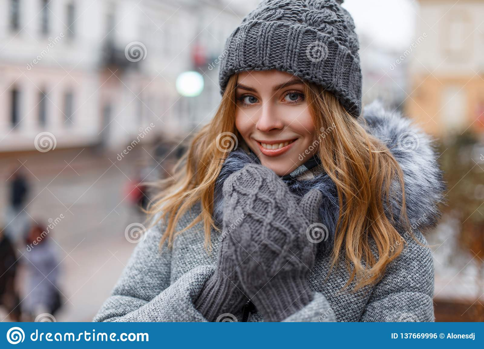 Portrait of a wonderful young woman with beautiful blue eyes with natural make-up in a sweet smile in a knitted hat