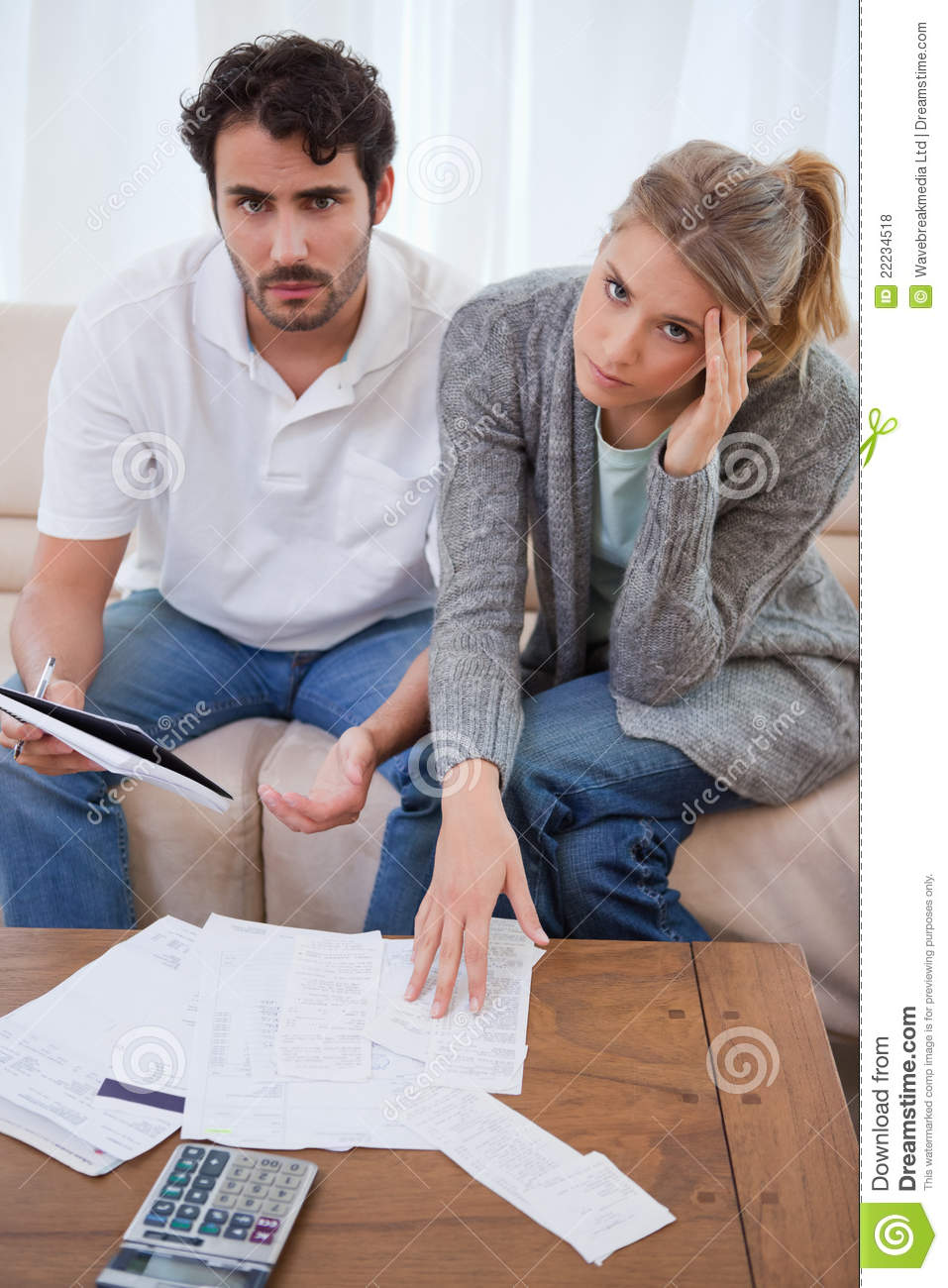 Portrait of a worried young couple looking at their bills