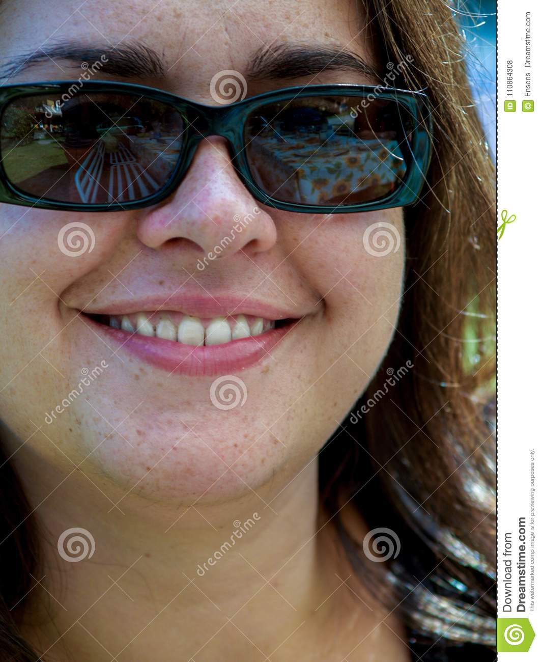 Portrait of 30 year old girl with dark glasses alone, smiling an