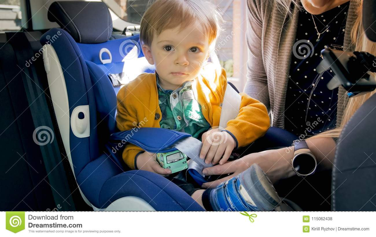 Portrait Of 2 Years Old Baby Boy Sitting In Car Safety Seat And Holding A Toy