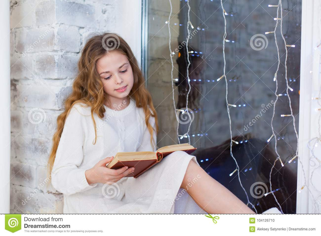 Portrait of 10 years old child reading book on the window on christmas.